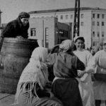 Работники столовой скатывают бочку с пивом